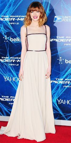 Emma Stone debuted her new bangs at the New York City premiere of The Amazing Spider-Man 2 in an elegant nude Prada gown lined with edgy gunmetal piping. For accessories, she selected Sidney Garber jewelry.