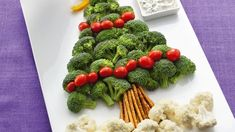 """A broccoli and tomato """"tree"""" with pretzel """"trunk"""" and cauliflower """"snow"""" are delicious dippers for a cool and creamy dip."""
