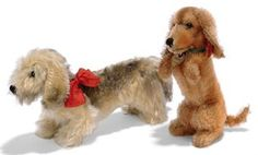 A STEIFF WIREHAIRED DACHSHUND AND BEGGING WALDI, standing Wirehaired Dachshund , (1315,0?), black-tipped long maize mohair, black glass eyes, black stitching, inoperative squeaker, green collar, red bow and FF button, circa 1939 --8¾in. (22.5cm.) high; and a begging Waldi, (4317), reddish brown mohair, black glass eyes, black stitching, swivel head, inoperative squeaker, green collar, card tag and FF button with red cloth tag, circa 1934 --6¾in. (17.5cm.) high (slight fading)
