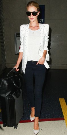 Rosie Huntington-Whiteley breezed through LAX with her impeccable model off-duty wardrobe intact—she topped off her plain white tee and black skinnies with a sleek structured printed white blazer, oversize shades, a single pendant, and white pumps.