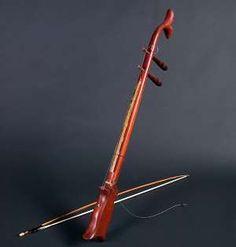 K'NI. Cordófono frotado, fabricado a partir de una caña de bambú. La caña hace las veces de diapasón.  Instrumento sin caja de resonancia, pues un hilo tenso, rematado con una escama de pescado, un fragmento de cuerno de búfalo u otro elemento rígido, comunica el puente con la boca del intérprete. Éste, altera la cavidad de la misma, modificando el color del sonido.   https://youtu.be/f9WVTb83KUM