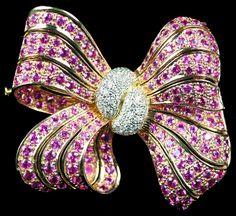 Pink Sapphire & Diamond Bow Brooch. Accompanied by 13.19 carats of Pink Sapphires and 1.00 carat of Diamonds. Set in 18 karat Rose Gold.
