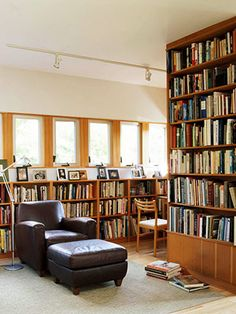 Here, a freestanding bookcase is used as a room divider, and low bookshelves run along a wall under windows.