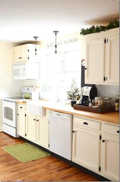 iron and twine kitchen (8) - I like the beadboard ceiling and the white (cream?) cupboards with black hardware.