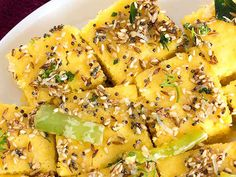 Khaman+Dhokla 1 cup  (Besan 1 tablespoon sooji) 1½ teaspoons Lemon juice 1 teaspoon Eno Fruit Salt 1 teaspoon crushed Green Chilli-Ginger 3/4 cup Water 1/4 cup Curd  1 teaspoon Oil (for greasing) Salt For Tempering: 2 T Oil 10-15 Curry Leaves 1/2 t rai  1 t  til 1T Sugar 4 Green Chillies, 2T Coriander Leaves 2T grated Fresh Coconut 1 pinch (hing) 1/2 cup Water