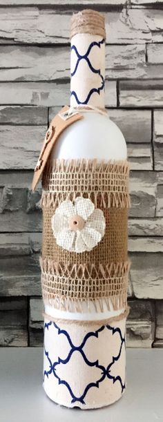 Recycled rustic decorative Wine Bottle painted white embellished with burlap and linen flower. Perfect centerpiece for your house and office. Measurements 13 in Tall x 9.05 in diameter.