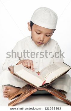A little muslim boy wearing islamic attire reading the holy Quran by Hasnuddin, via Shutterstock