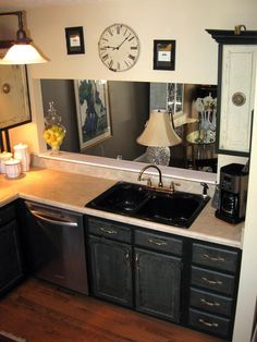 An ebony sink stands out against the cream counters in this kitchen, which has a peekaboo wall opening that offers a view of a dining room. A large clock with Roman numbers is on the wall above this wall opening.