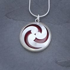 """Fire Within Pendant 4 from Sarah McCulloch Designs.  Empowering and bold, this pendant will surely express your unique spirit and passion. The pierced sterling silver reveals a layer of vibrant, flame-patinated copper. 1.25"""" in diameter and ⅜"""" deep, domed by hand and set in a sterling silver bezel. Available with a 16"""" or 18"""" sterling silver snake chain."""