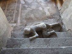 VII.16.17-22 Pompeii. December 2007. Plaster cast of body lying at foot of staircase. Four people met their death in this house, three of them died huddled together on this staircase. They were discovered in November 1961. It was possible to make casts of the group of three. The lowest of the three bodies remains where it was discovered. The fourth skeleton was lying on the landing at the bottom of the stairs but only a photo remains of this skeleton.