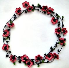Burgundy flowers and green leaves are crocheted around black crochet necklace…