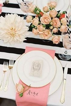 Black and white striped wedding table runner on a modern tablescape with white dahlias and blush roses and pink place settings.