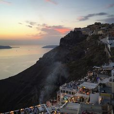 An incredible sunset over the clifftops of Santorini, Greece. You can see the whitewashed restaurants and all the curious tourists who have gathered to view one of the worlds most famous sunsets.
