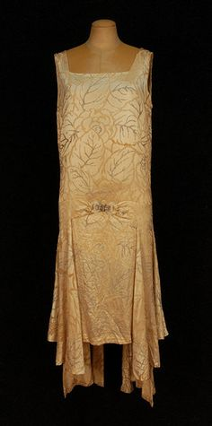 1920's. MOLYNEUX BEADED CREAM SILK EVENING DRESS,  Sleeveless with square neckline, dropped waist having overskirt at sides with spade shaped gores joined at front by a jeweled buckle, the back having applied crossed bands flaring below the hem, allover decorated with branches in pearls and crystal beads.