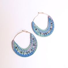 Crochet Hoop Earrings with beads variegated yarn in shades of blues, greens and purples.