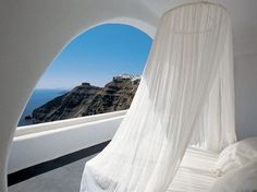 white net canopy bed and view of santorini, greece