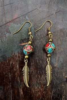 Feather- stands for hope, balance and good luck.  Beautiful ethnic earrings made of an Antique Bronze feather charm and handcrafted Nepali Brass bead Inlaid with turquoise and coral. Simply a beautiful jewelry.  ◢◢◢ ◣◣◣◥◤ ◢◢◢ ◣◣◣ D E T A I L S ◢◢◢ ◣◣◣◥◤ ◢◢◢ ◣◣◣ ◥◥◥ ◤◤◤◢◣ ◥◥◥ ◤◤◤ D E T A I L S ◥◥◥ ◤◤◤◢◣ ◥◥◥ ◤◤◤  *Light weight. *Bronze ear wires. Earrings measure 2.5 inches/ 6cm from top of ear wire. Bronze feather charm measure 1.2 inches.  All metals used are lead and nickel free!  *****...