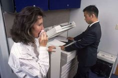 A woman coughs into a tissue as a co-worker makes copies - Aaron Haupt/Getty Images