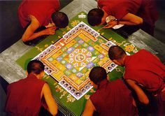 """Tantric Buddhist Mandala sand paintings are painstakingly poured grain by grain using a small funnel. Mandala is a Sanskrit word meaning cosmogram or """"world in harmony."""