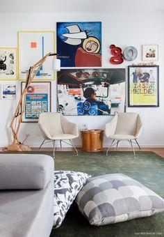 Sala de estar com parede repleta de quadros, cantinho de leitura e almofadões.