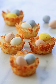 Coconut macaroons shaped like a bird's nest, filled with mini chocolate Cadbury eggs. An tasty Easter treat! These were inspired by this month's Martha Stewart