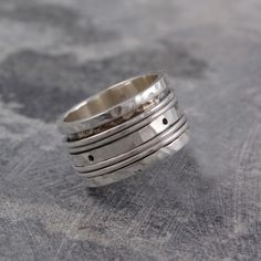 Hammered Silver Spinning Ring - A stunning and truly unusual design which combines contemporary style with a playful, tactile element. This Hammered Silver Spinning Ring is impossible not to twiddle! Also available in large sizes making this an unusual Silver Ring for Men. #Otisjaxon #Jewellery