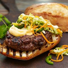 This burger features a ginger and garlic seasoned grilled patty, crisp Asian slaw, spicy Sriracha mayonnaise and fresh cilantro and mint to cool the heat.