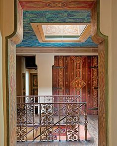 """The upstairs hall with its ironwork railings and scored oak floor features decorative painting by two Danish artists who spent a year accenting doorways, ceilings, and furniture. The linen closet doors are adorned with trompe l'oeil """"carvings. Spanish Interior, 1920s House, Spanish Colonial, Spanish Revival, Desert Homes, Iron Furniture, Painted Doors, Painted Walls, Hand Painted"""
