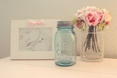 nursery vignette...only mason jar would have something useful/functional in it. cotton balls, lotion, pacifiers, anything with a storage purpose.    the pink bow looks tacky on the frame, but the fresh flowers and mason jar with frame is beautiful.