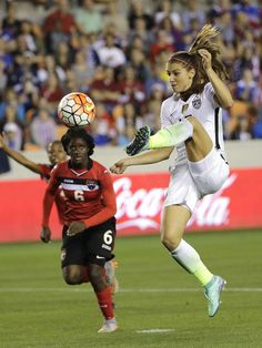 United States' Alex Morgan (13) shoots and scores a goal as Trinidad and Tobago's Khadidra Debesette (6) defends during the second half of a CONCACAF Olympic women's soccer qualifying championship semifinal. David J. Phillip, AP