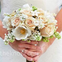 Bridal bouquet of stephanotis with sahara roses, tulips, lilacs, and lilies of the valley, all wrapped in ivory ribbon
