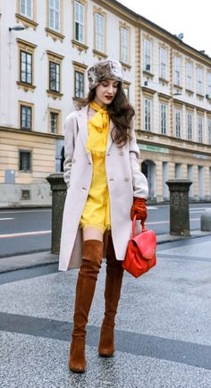 Fashion Blogger Veronika Lipar of Brunette from Wall Street sharing how to wear yellow dress in winter | otk suede brown boots, fur cap, red purse, light tan pea coat