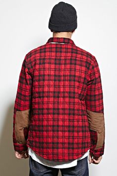 A quilted plaid jacket by Cohesive & Co.™ featuring a basic collar framed by a subtle contrast plaid panel, a buttoned front, a chest patch pocket with a single pen holder, button-cuff long sleeves, contrast elbow patches, and on-seam side pockets.