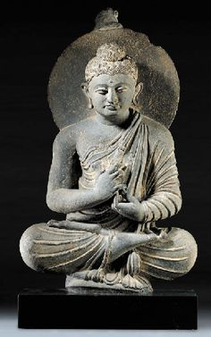 A Gray Schist Figure of Buddha   Gandhara, circa 4th Century   Seated in dhyanasana with his arms crossed before his chest in the gesture of teaching, dharmachakra mudra, wearing long flowing robes draped across his left shoulder, his face with a meditative expression and wavy hair rising to a domed topknot and backed by a nimbus  23¾ in. (68 cm.) high