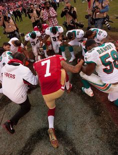 Members of the Miami Dolphins and San Francisco 49ers kneel in prayer following an NFL football game, Sunday, Dec. 9, 2012
