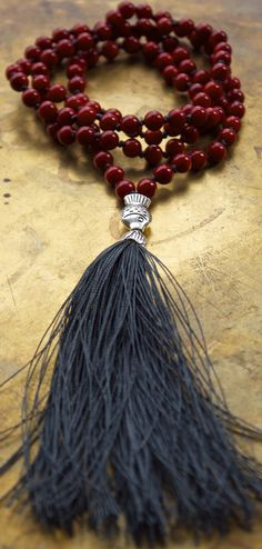 Red coral mala beads with a sterling fish charm.
