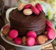 Esse bolo da Soul Sweet (http://soulsweet.com.br/) tem cobertura de ganache e macarons em tons de rosa, soltos no topo e no prato