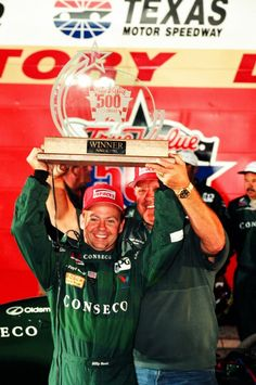 June 6, 1998: Billy Boat, driver of the No. 11 Conseco A.J. Foyt Racing Dallara Oldsmobile Aurora, holds the winner's trophy in Victory Lane with A.J. Foyt after winning the Indy Racing League True Value 500.