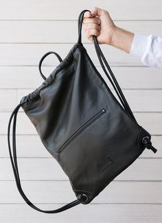 "Soft drawstring backpack features exterior zippered pocket and leather hanging loop. Made in USA Materials: Full grain leather, polycotton twill lining Size: (W) x 17 ½"" (H) x ½"" (D) Backpack Bags, Drawstring Backpack, Leather Backpack, Leather Bag, Backpack Pattern, String Bag, Fabric Bags, Leather Accessories, Handmade Bags"