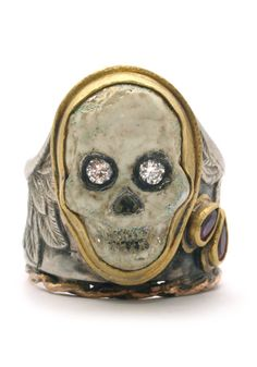 A carved stone, gem-set skull, set in a gem-set silver and gold ring.