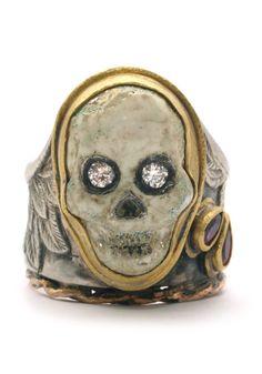 A carved stone, gem-set skull, set in a gem-set silver and gold ring.