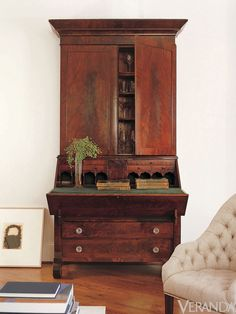 """""""I love a monumental secretary in a white space,"""" says Carter. Despite its size, he says, the piece pictured above could easily be lost in a wallpapered room. Carter uses neutral paint not only to showcase antique elements, but to add an avant garde touch. """"People often tell me that my rooms are very modern,"""" he says, """"but generally they are populated with a lot of antiques.""""   - Veranda.com"""