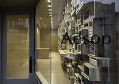 Aesop store in San Francisco by NADAAA with reclaimed timber boxes piled up to the ceiling to create a wall of shelves.