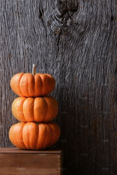 Mini Decorative Pumpkins A Stack Of Three Against Rustic Wood Background
