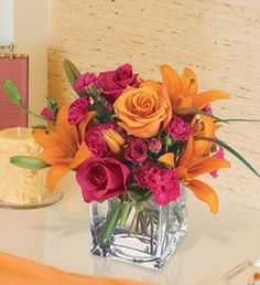 """Uniquely Chic "" - bright pink and orange flowers in cube vase"