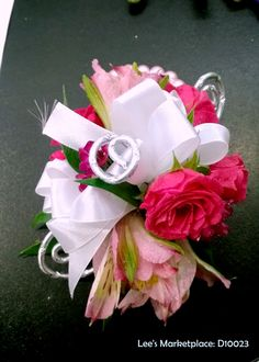 corsage | pink mini roses, pink lisianthus, pink waxflower, white satin ribbon with silver diamond wire twirls