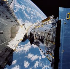 On April 24, 1990, the Hubble Space Telescope launched. It was deployed on April 25, as seen in this photograph taken by the crew of the STS-31 space shuttle mission, the Hubble Space Telescope is suspended above shuttle Discovery's cargo bay some 332 nautical miles above Earth.