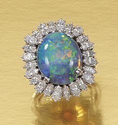 OPAL AND DIAMOND RING. Designed as a cluster, set to the centre with an oval opal within a surround of marquise-shaped diamonds, size M, sizing band.