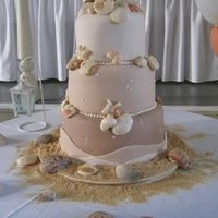 Fondant covered cake with graduating  shades of brown.   Fondant/Gumpaste mix for sea shells, fondant scalloped border and vanilla wafer crumbs for sand.   This cake was picked up by a bride who travelled by car around 8 hours and then by boat to get to her wedding destination.   It travelled great!