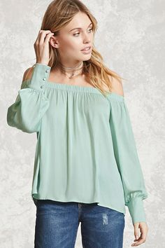 A satin top featuring an elasticized off-the-shoulder neckline, long sleeves with buttoned cuffs, and a flowy silhouette.